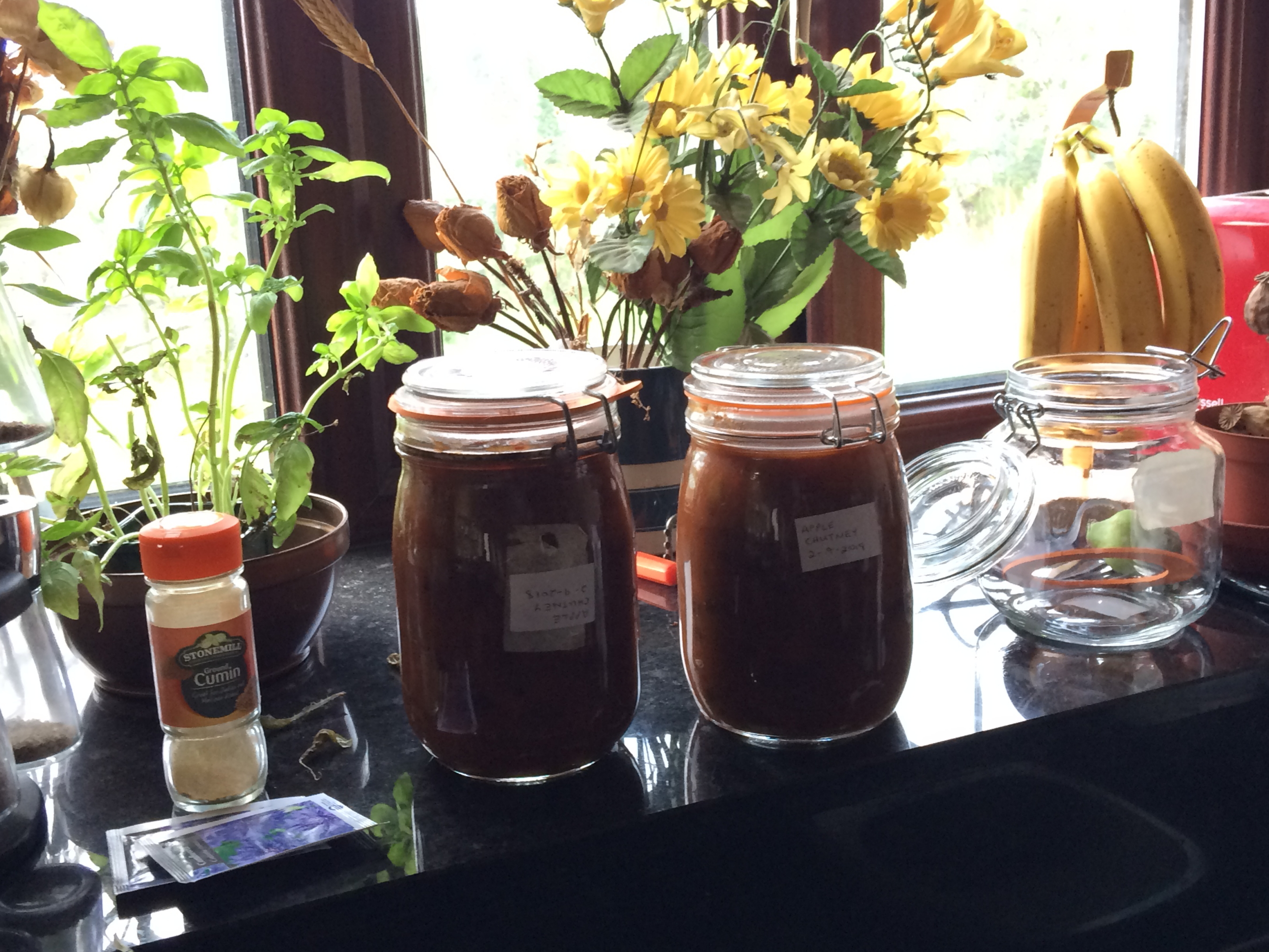 Two 1 litre jars of apple chutney on window cill